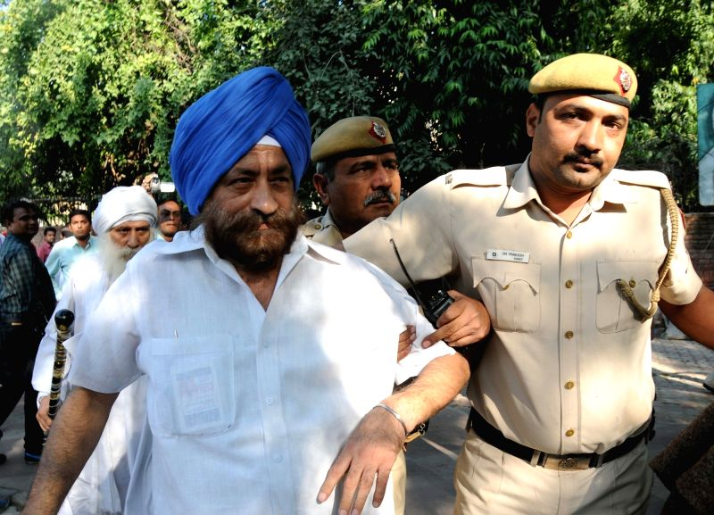 Author Gurcharan Singh Babbar who along with others was staging a demonstration against delay in justice for the 1984 riot victims, being taken away by police at Jantar Mantar in New ...