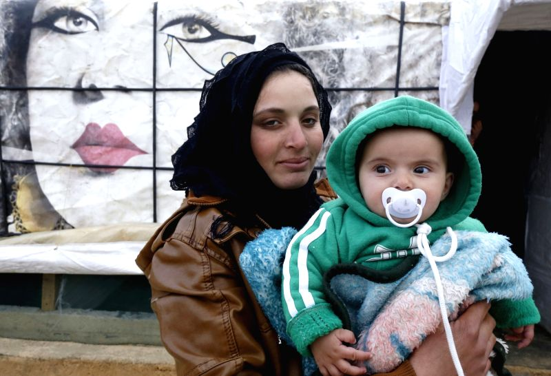 BAALBEK (LEBANON), Dec. 10, 2018 A Syrian woman holds her baby at a refugee camp near the Baalbek City in Lebanon's eastern Bekaa valley, Dec. 10, 2018. The Syrian refugees in the camp ...