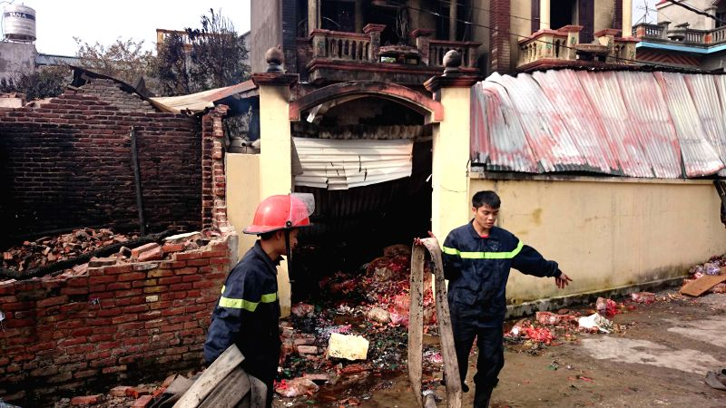 Firefighters work at the fire site in Bac Ninh province, north Vietnam, Dec. 15, 2014. The fire occurred at midnight on Dec. 14 at a shop trading votive paper, ...