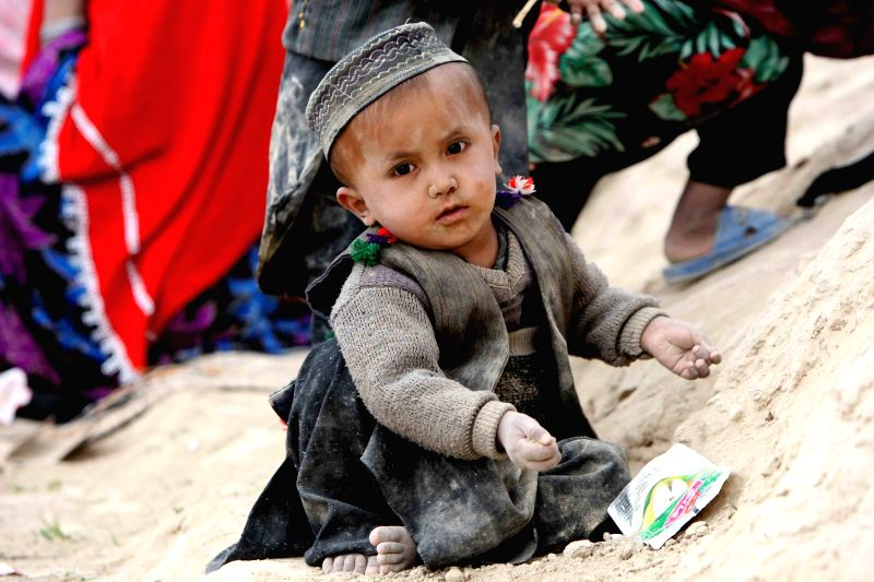An Afghan child plays on the ground after a landslide in Badakhshan Province of northern Afghanistan on May 3, 2014. Up to 255 victims were identified out of ...