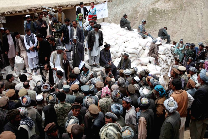 Afghans wait to receive relief food after landside in Badakhshan province, northern Afghanistan, May 4, 2014. The deadly landslide occurred Friday in the ...