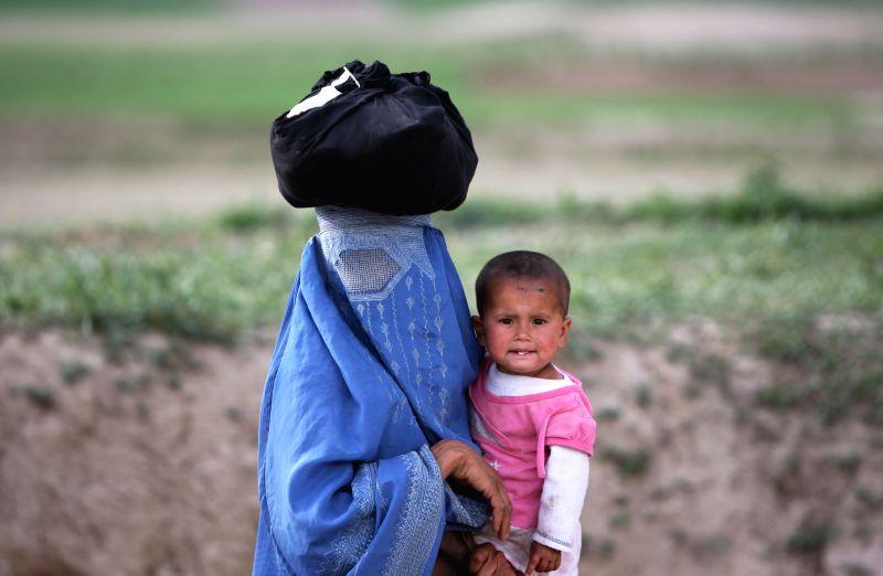 An Afghan woman holds her daughter on a road in Badakhshan province in northern of Afghanistan, May 6, 2014.