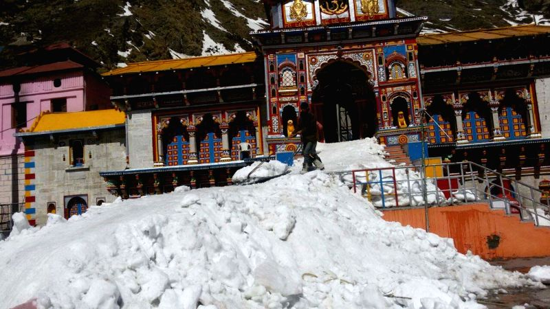 A worker busy cleaning the premises of Badrinath temple which is coverad with snow after heavy snowfall on April 18, 2015.