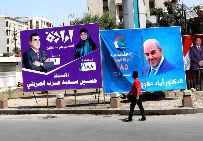 BAGHDAD, April 14, 2018 - An Iraqi man passes by campaign posters in downtown Baghdad, Iraq on April 14, 2018. Iraq is scheduled to hold its parliamentary elections on May 12, which will be the first ...