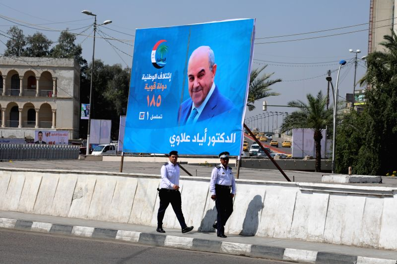 BAGHDAD, April 14, 2018 - Two policemen walk past a campaign poster in downtown Baghdad, Iraq on April 14, 2018. Iraq is scheduled to hold its parliamentary elections on May 12, which will be the ...