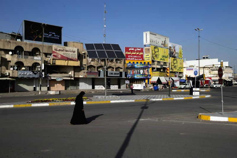 A woman walks in an empty street in downtown Baghdad, capital of Iraq, on April 29, 2014, one day ahead of the country's parliamentary election. This is the first .