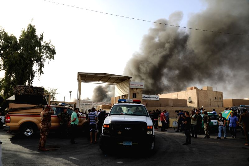 BAGHDAD, June 10, 2018 - Iraqi security forces and firefighters gather as smoke surges from warehouses in Baghdad, Iraq, June 10, 2018. A massive fire broke out Sunday in three warehouses containing ...