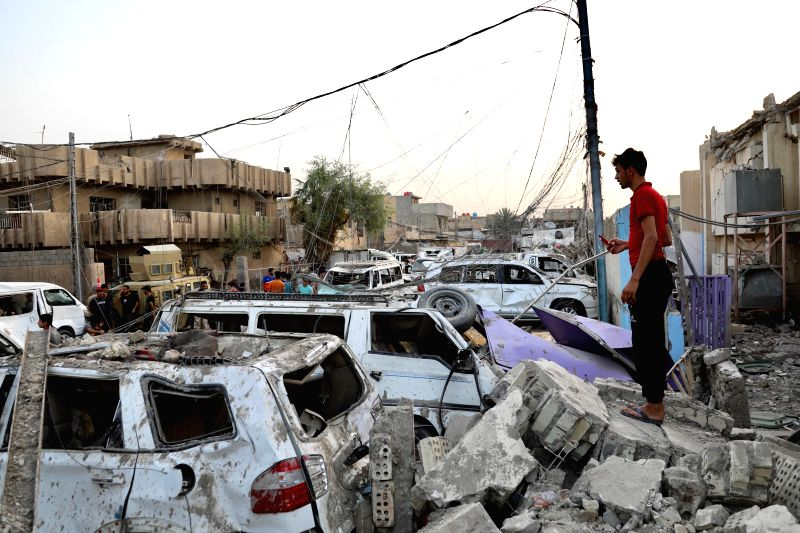 BAGHDAD, June 7, 2018 - A man stands beside cars damaged at a huge explosion, in eastern Baghdad, Iraq, June 7, 2018. The death toll of a huge explosion in eastern Baghdad on Wednesday rose to 14, ...