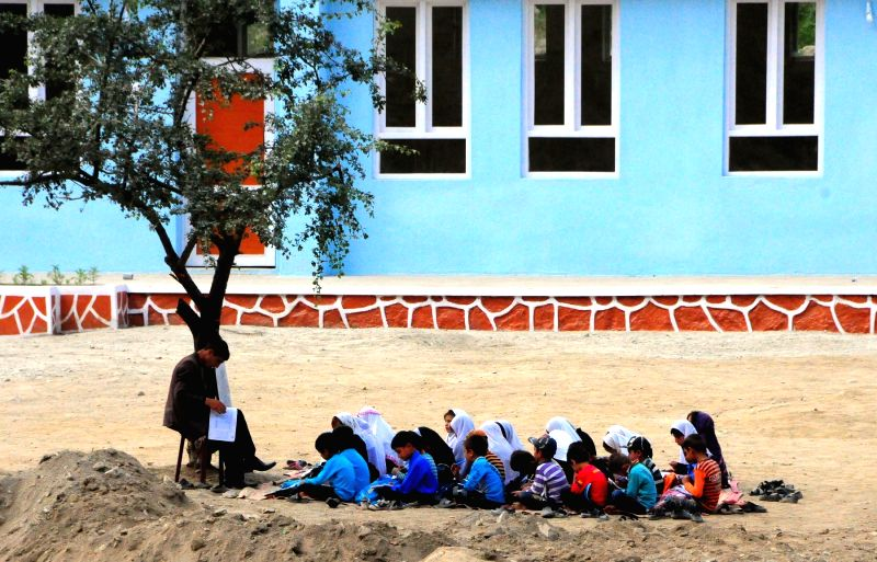 Children study outside without classrooms in Baghlan province, northern Afghanistan, on June 19, 2014. In Afghanistan, 4 million children have no access to school ..