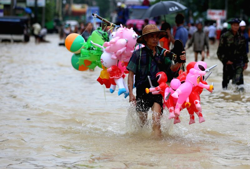 BAGO, July 28, 2018 - A balloon seller wades through flood water in Bago Region, Myanmar, July 28, 2018. People in Bago Region are being affected by flood due to the continuous heavy rainfall.