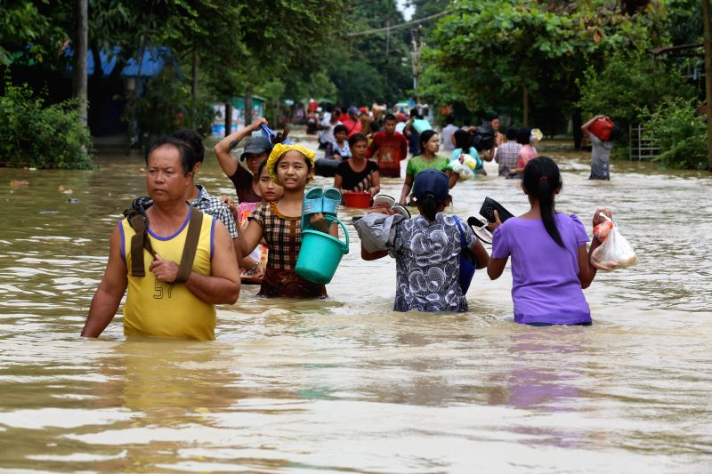 BAGO, July 28, 2018 - Residents wade through flood water in Bago Region, Myanmar, July 28, 2018. People in Bago Region are being affected by flood due to the continuous heavy rainfall.