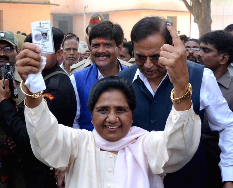 Bahujan Samaj Party chief Mayawati shows her fore finger marked with phosphorous ink and voter's identity card after casting her vote at a polling booth during the seventh phase of 2014 Lok Sabha ...