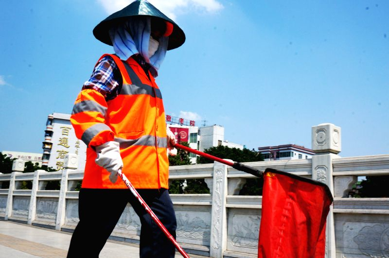 A sanitation worker shields himself from the hot sun as cleaning a road in Baise City, southwest China's Guangxi Zhuang Autonomous Region, May 14, 2014. A heat wave ...