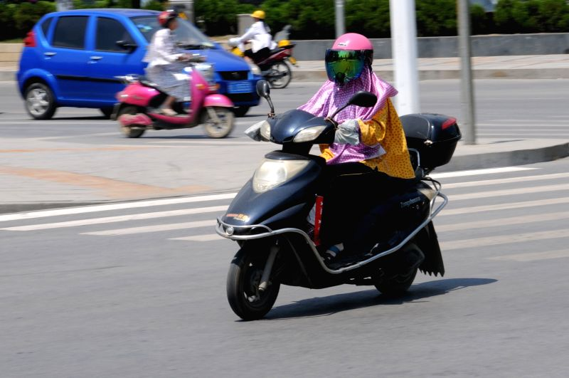 A woman shields herself from the hot sun as riding on a road in Baise City, southwest China's Guangxi Zhuang Autonomous Region, May 14, 2014. A heat wave hit the city .