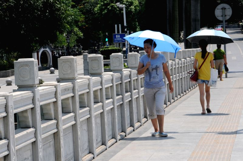Women shield themselves from the hot sun as walking on a road in Baise City, southwest China's Guangxi Zhuang Autonomous Region, May 14, 2014. A heat wave hit the city