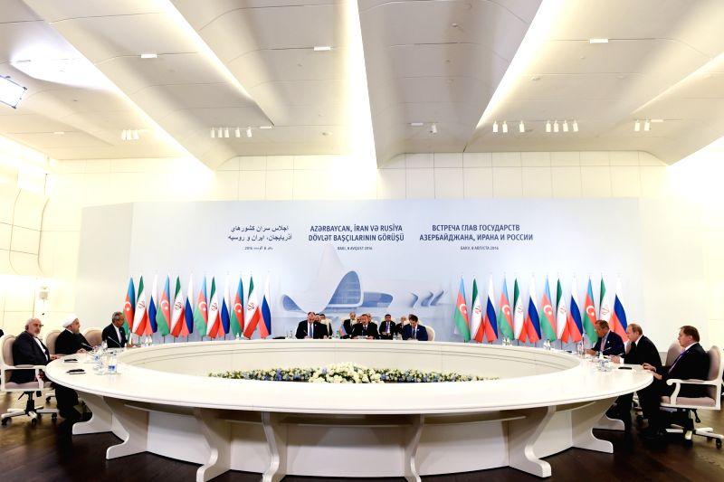 BAKU, Aug. 8, 2016 - Iranian President Hassan Rouhani (2nd L), Azerbaijani President Ilham Aliyev (C) and Russian President Vladimir Putin (2nd R) attend a trilateral meeting in Baku, Azerbaijan, ... - Hassan Rouhani