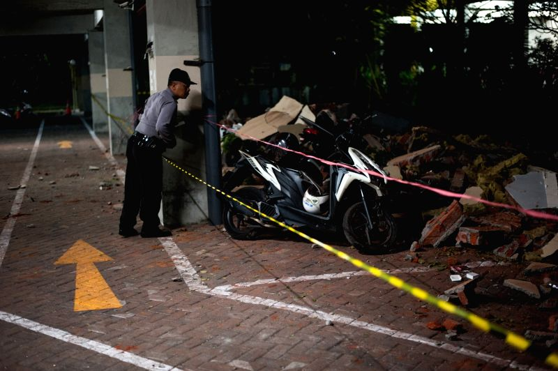 BALI (INDONESIA), Aug. 5, 2018 A security officer checks the rubble at a parking lot after an earthquake in Badung Regency, Bali, Indonesia, on Aug. 5, 2018. At least 37 people were ...