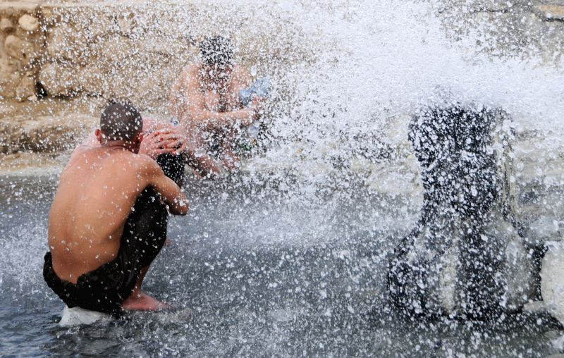 Afghan men enjoy in water fountain in Balkh province, northern Afghanistan, April 10, 2014.