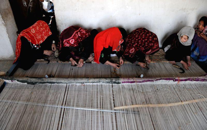 Women weave carpet in Balkh Province, east Afghanistan, on April 10, 2014.