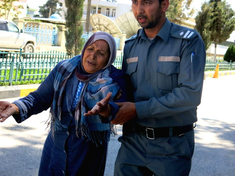 An Afghan policeman assists a wounded woman at the site of an attack in Balkh province, Afghanistan, April 9, 2015. At least four people were killed and several ...