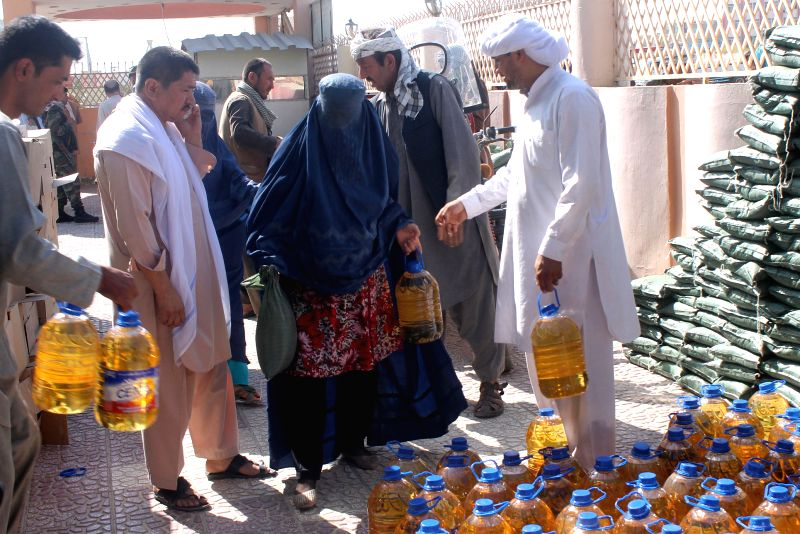 Afghans receive food donated by the rich during holy month of Ramadan in Balkh province in northern Afghanistan, July 22, 2014.