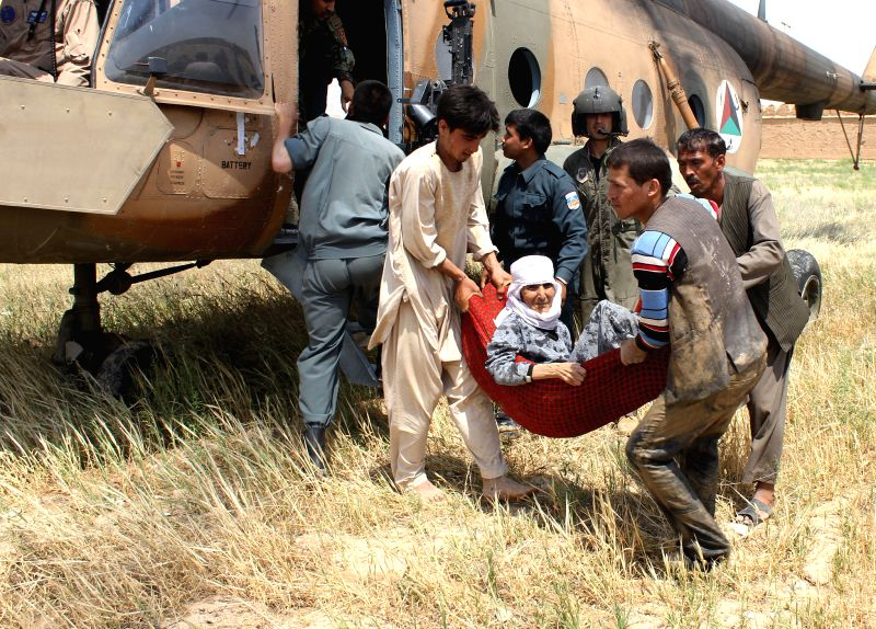 Afghan policemen transfer victims from flooded area in Balkh province in northern Afghanistan on May 12, 2014.