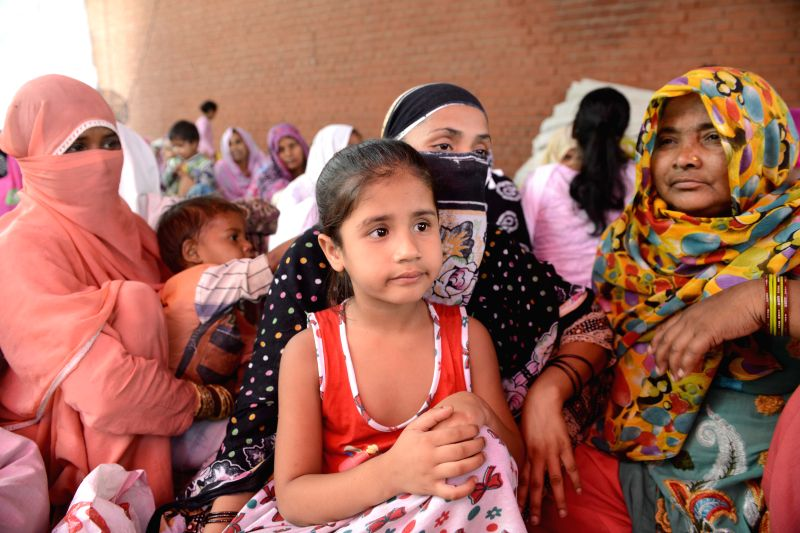 People take refuge in a Police Station after communal riots broke out in Ballabhgarh of Haryana on May 30, 2015.