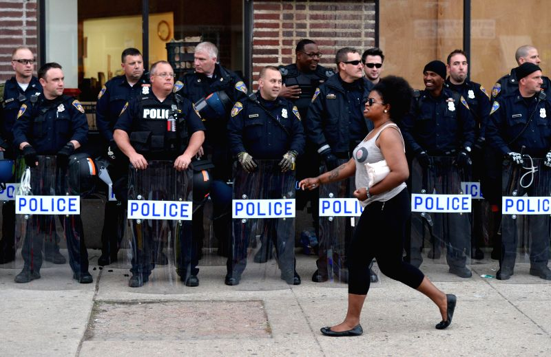 A womon walks by riots policemen in west Baltimore, Maryland, the United States, May 1, 2015. Maryland state prosecutor on Friday announced criminal charges against ...