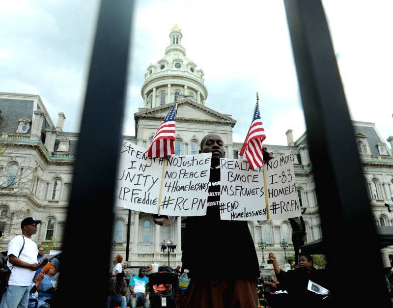 A man holding signs attends a rally in front of the City Hall in Baltimore, Maryland, the United States, May 2, 2015. Thousands of people in Baltimore, the largest ...