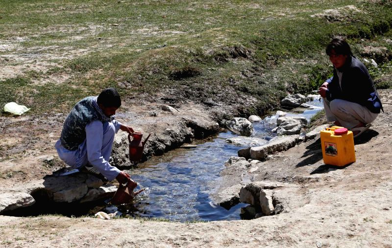 Afghan men get water from a canal in Bamyan province in central Afghanistan on April 22, 2014.