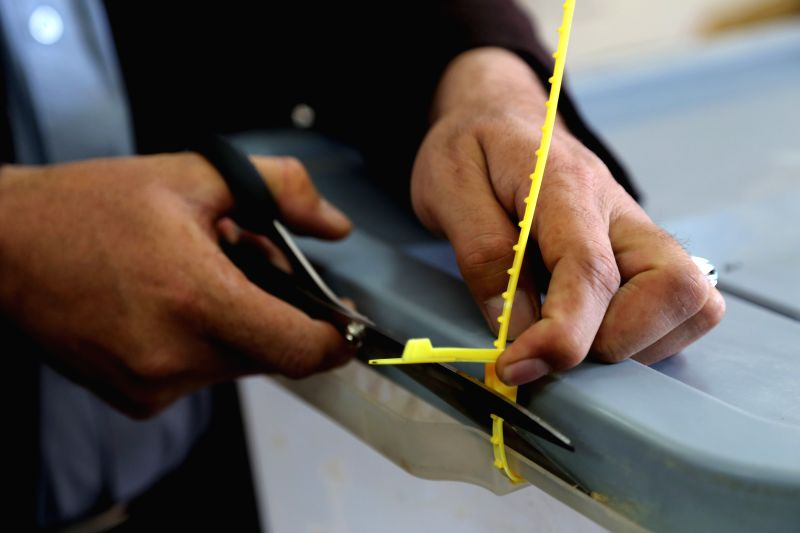 An Afghan election worker cuts a ballot box log before countings at an election office in Bamyan province in central Afghanistan on April 22, 2014. More than 3.4 ...