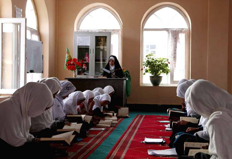 Afghan girls read the Quran at a mosque during the Muslim fasting month of Ramadan in Bamyan, central province of Afghanistan, July 10, 2014.