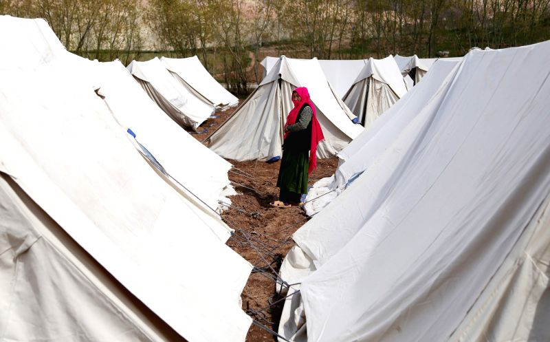 An Afghan displaced woman walks outside the tents in Bamyan province in central Afghanistan on May 12, 2014.
