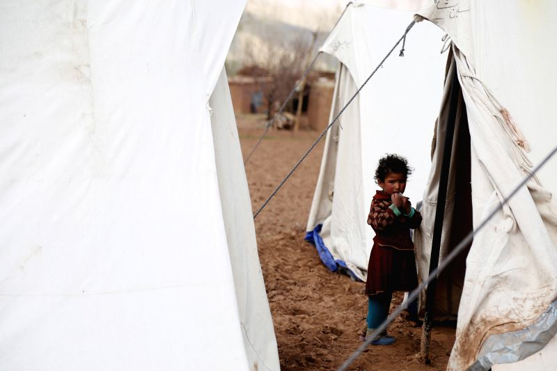 An Afghan displaced child stands outside a tent in Bamyan province in central Afghanistan on May 12, 2014.