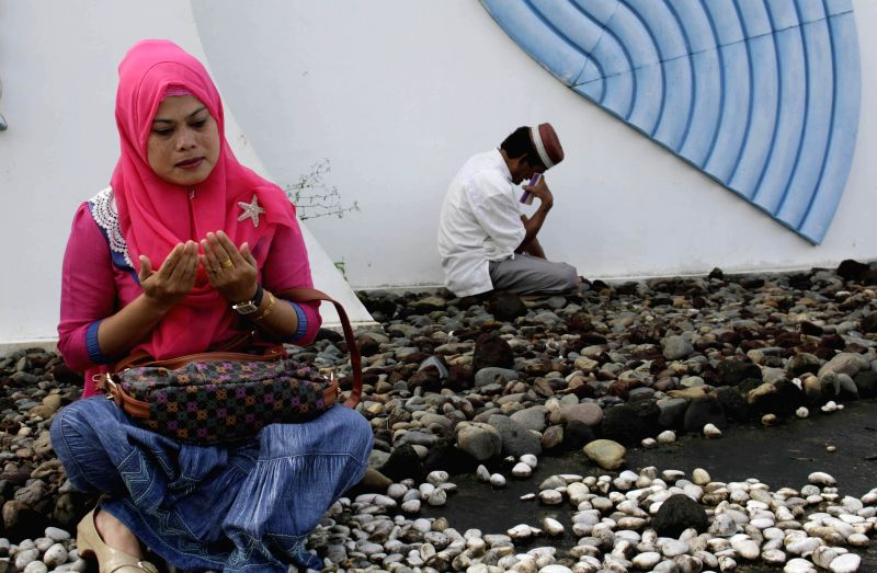 An Indonesian Muslim woman sow flowers during the commemoration of 10th anniversary of the devastating tsunami at Ulee Lheue mass grave in Banda Aceh, Indonesia,