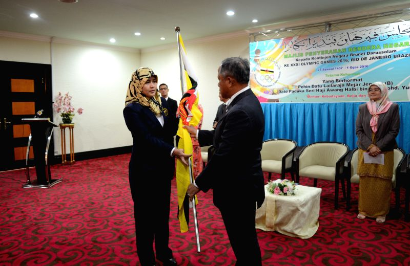 BANDAR SERI BEGAWAN, Aug. 1, 2016 Xinhua)Photo taken on Aug. 1, 2016, shows Hj Awang Halbi (R, front), Brunei's Minister of Culture, Youth and Sports presenting the national flag to Brunei's ...