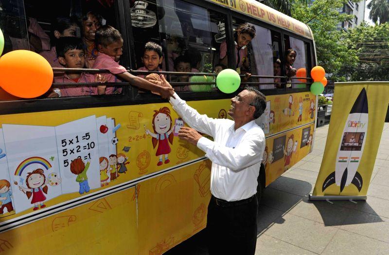 "Bandhan Bank Managing Director Chandra Shekhar Ghosh with children on ""Kalam Library on Wheels"" in Kolkata, on May 12, 2016. - Chandra Shekhar Ghosh"