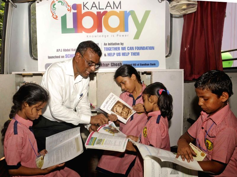 "Bandhan Bank Managing Director Chandra Shekhar Ghosh with children on ""Kalam Library on Wheels"" in Kolkata, on May 12, 2016. - Chandra Shekhar Ghosh"