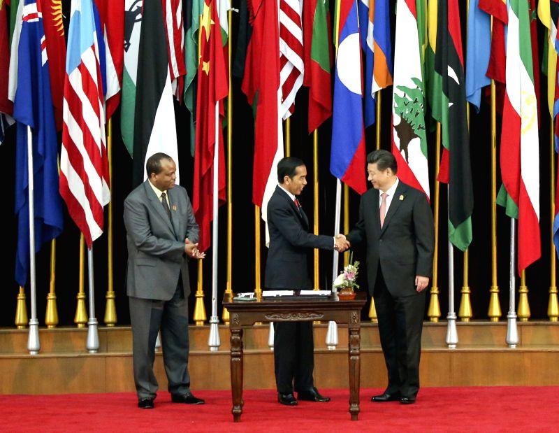 Chinese President Xi Jinping (R), Indonesian President Joko Widodo (C) and Swaziland King Mswati III sign into effect the Bandung Message, in Bandung, Indonesia, ...