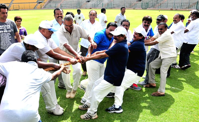 Bangalore Mayor B S Satyanarayana during and other BBMP councilors participate in a tug-of-war during Mayor Cup cricket match at M. Chinnaswamy Stadium in Bangalore on June 22, 2014.