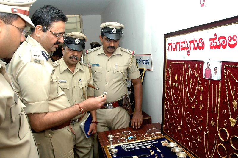 Bangalore Police Commissioner Raghavendra Auradkar inspects the stolen jewellery recoverd during a press conference at his office in Bangalore on  May 8, 2014.