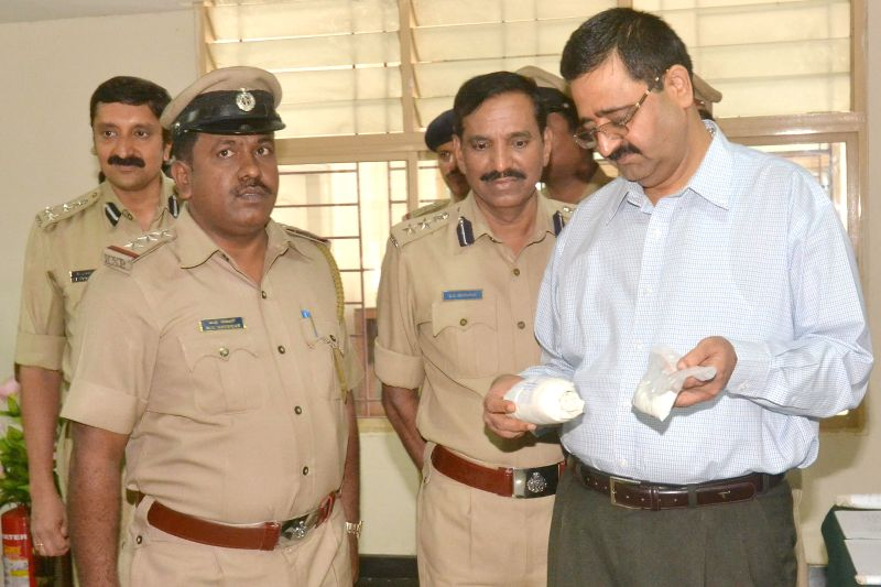 Bangalore Police Commissioner Raghavendra Auradkar takes a look at a Brown Sugar packet worth 45 Lakhs which was recovered by the police, during a press conference in Bangalore on July 1, 2014.