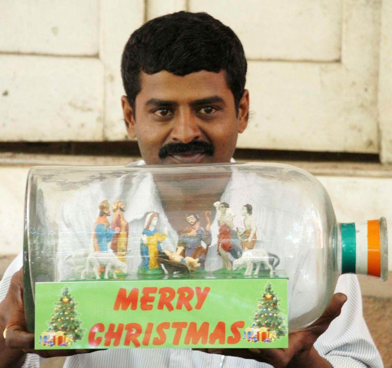 Bottle artist Basavaraj S Gowda displays his creativity by placing the nativity scene inside a bottle on the eve of Christmas, in Bengaluru on Dec 24, 2014. - Basavaraj S Gowda