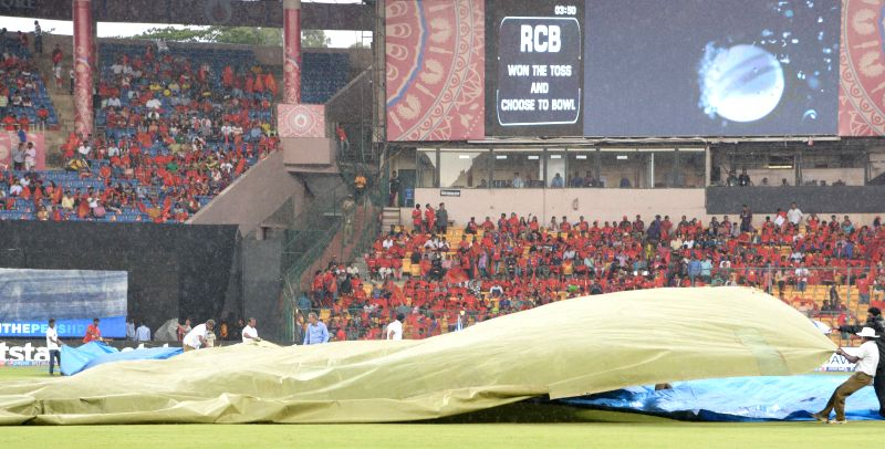 Ground staff at work as rain disrupts an IPL-2015 match between Royal Challengers Bangalore and Kolkata Knight Riders at M Chinnaswamy Stadium in Bangaluru on May 2, 2015.