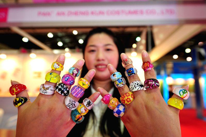 A woman shows fashion rings from China at the 5th China products show 2014 at IMPACT Muang Thong Thani in Bangkok, Thailand, Nov. 20, 2014.
