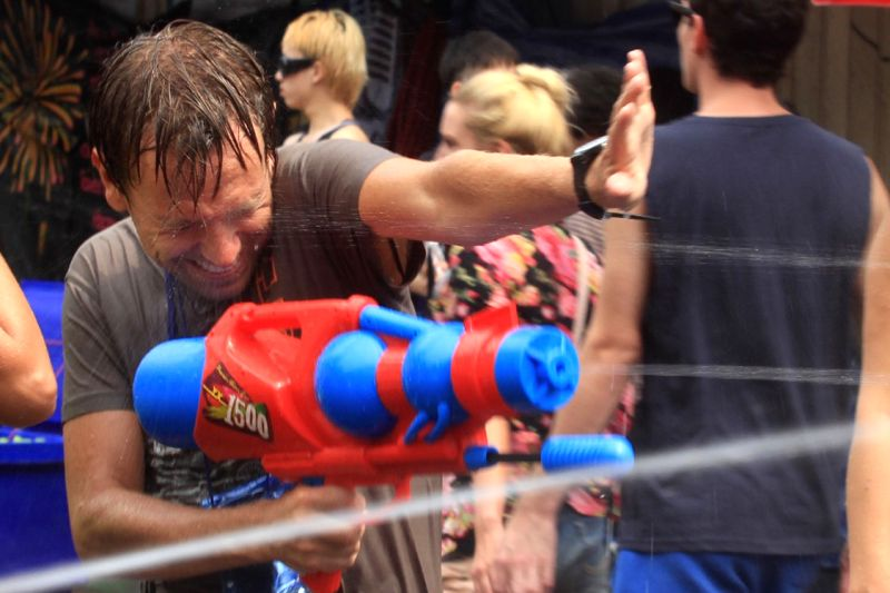 A tourist takes part in a water gun battle during celebrations for Songkran Festival, in Bangkok, Thailand, April 12, 2014. Songkran Festival, also known as water .