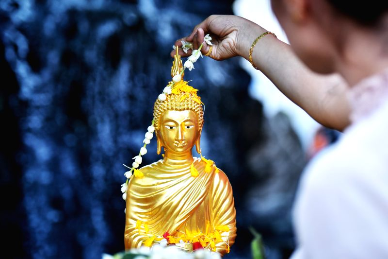 A worshiper decorates a Buddha statue with a flower wreath in the run-up to Songkran at Wat Pho in Bangkok, Thailand