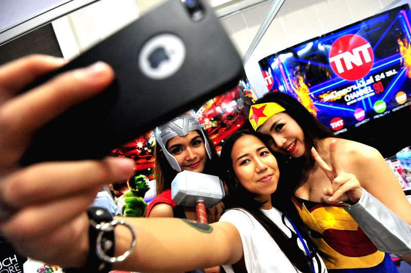 BANGKOK, April 21, 2017 - A visitor (C) poses for a selfie with two cosplayers during Thailand Comic Con 2017 in Bangkok, Thailand, April 21, 2017. Thailand Comic Con 2017, a three-day event that ...