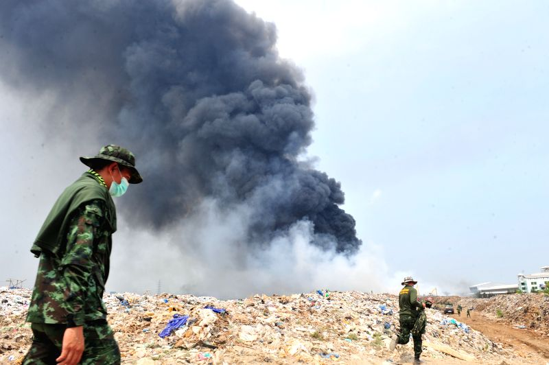 Thai soldiers walk at a garbage disposal site during a fire in Bang Phli district, on the outskirts of Bangkok, Thailand, April 22, 2015. (Xinhua/Rachen ...