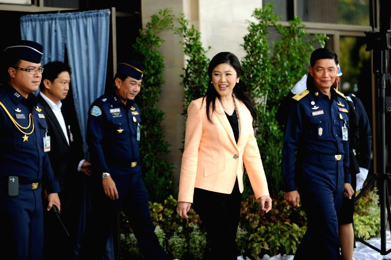 Thai caretaker Prime Minister Yingluck Shinawatra (2nd R) arrives for a meeting with the Election Commission (EC) at the Royal Thai Air Force Academy in Bangkok, ..